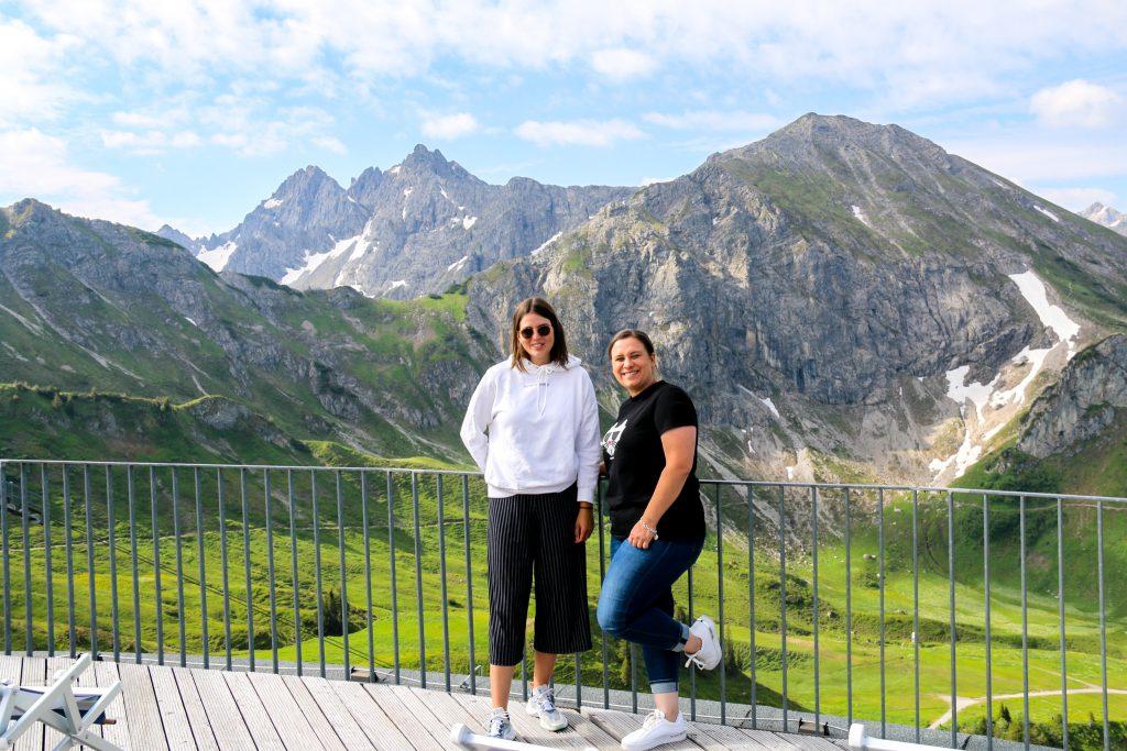 Tia und Steffi auf der Kanzlwand Aussichtsplattform mit den Allgäuer Alpen im Hintergrund.