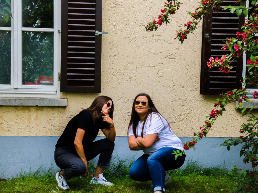 Steffi und Tia kniene vor einer Jugendherberge